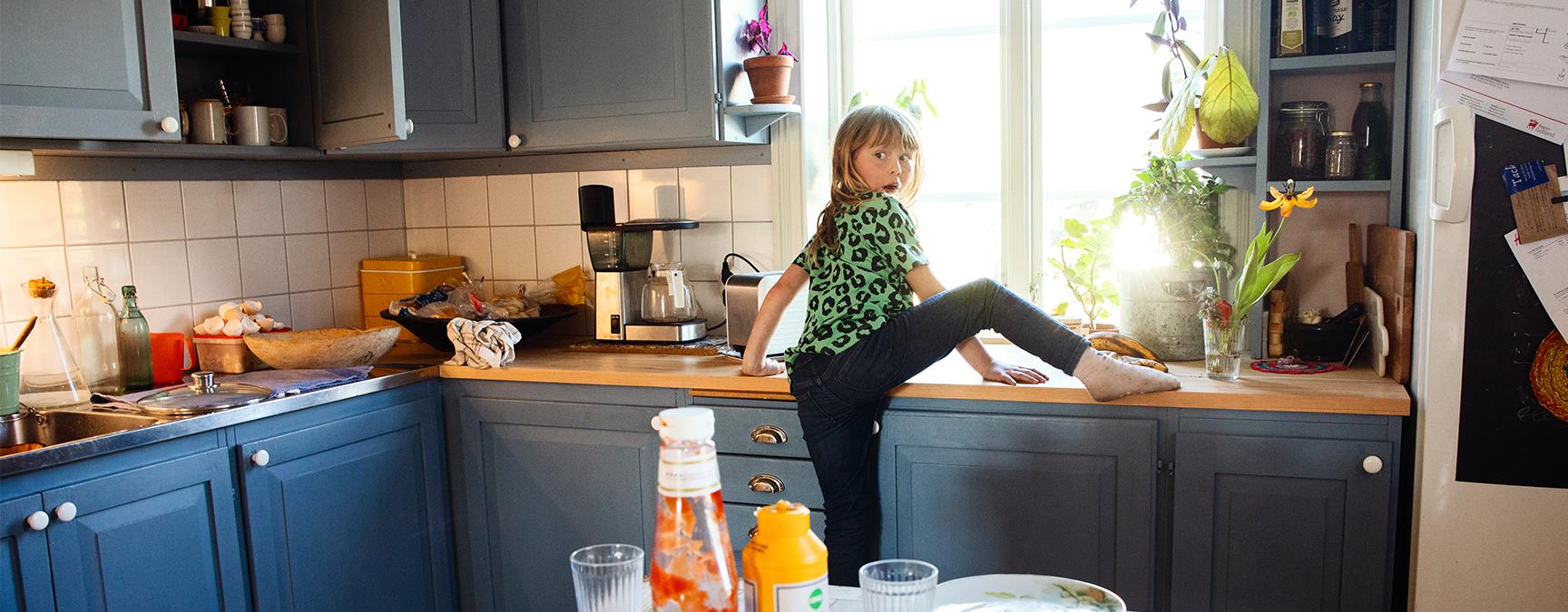 En busig flicka klättrar upp på en diskbänk.